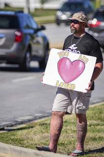 Mike Moore | The Journal Gazette Doug Ahr spreads a kind message on Saturday to motorists along Maplecrest Road.