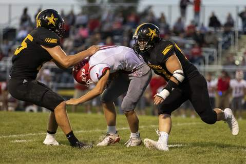 Photos by Josh Gales | The Journal Gazette Adams Central's Ryan Black is sacked by South Adams seniors Nick Miller, left, and  Austin Gorney during the second quarter of Friday night's game in Berne.