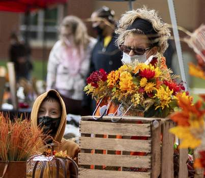 Rachel Bellwood | The Journal Gazette Shoppers peruse the wares Wednesday eveningat New Haven's Fall Market. The open-air market event at Schnelker Parkfeatured fall produce, fall crafts, baked goods and contests. (RACHEL BELLWOOD)