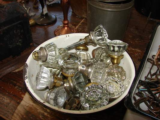 A bowl of old glass doorknobs is some of the door hardware available for reuse.