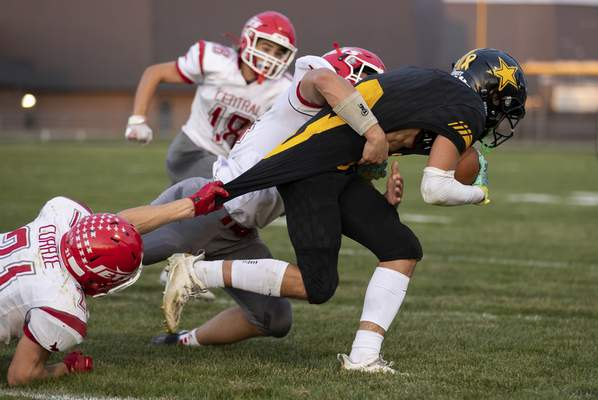 Josh Gales | Journal Gazette South Adams senior Drew Stutzman is brought down by Adams Central junior Alex Currie, left, and Adams Central junior Blake Heyerly, center, during the first quarter of the game at South Adams High School on Friday.