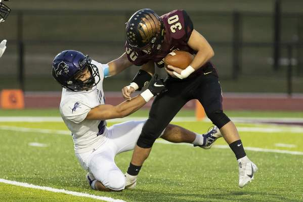 Josh Gales | Journal Gazette Columbia City junior Abe Barrera is tackled by Leo junior Carson Hoeppner during the first quarter of the game at Columbia City High School on Friday.