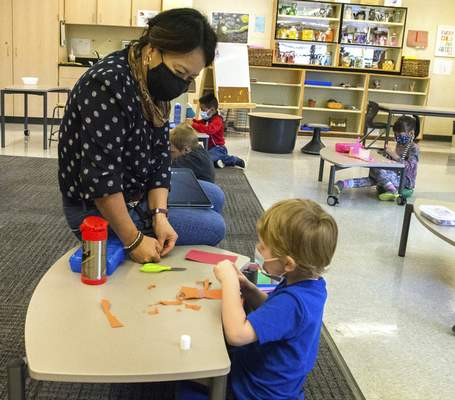 Michelle Davies   The Journal Gazette Andrea Jones, a teacher at Whitney Young Early Childhood Center, works with student Rhys Johnson on cutting and pasting.