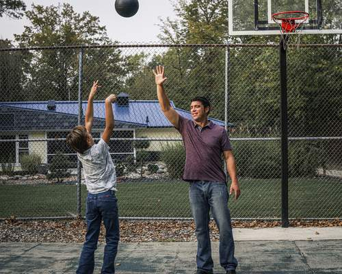 Photos by Mike Moore | The Journal Gazette Traxx and his stay-at-home dad, Eric Holsworth, play basketball in their backyard.