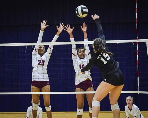 Mike Moore | The Journal Gazette Concordia defenders Taylor Hepburn, left and Mya Williams, center guard the net as  Leo junior Payton Rolfsen hits the ball in the first period during the IHSAA Volleyball Sectional at Bishop Dwenger on Tuesday.