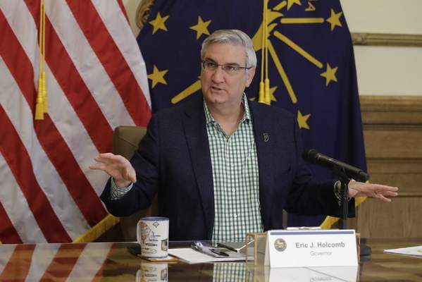 FILE - In this April 29, 2020, file photo, Indiana Gov. Eric Holcomb prepares to host a virtual media briefing in the Governor's Office at the Statehouse to provide updates on COVID-19 and its impact on Indiana, in Indianapolis. (AP Photo/Darron Cummings, File)