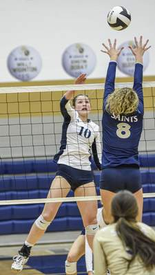 Mike Moore | The Journal Gazette Woodlan sophomore Avah Smith spikes the ball in the second period against Dwenger on Thursday during the IHSAA Volleyball Sectional at Bishop Dwenger High School.