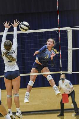 Mike Moore | The Journal Gazette  Dwenger sophomore Lexa Zimmerman spikes the ball in the first period against Woodlan on Thursday during the IHSAA Volleyball Sectional at Bishop Dwenger High School.
