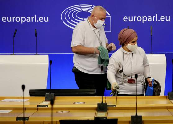 Members of the cleaning crew sanitize a room prior to a media conference of Sinn Fein's President Mary Lou McDonald at the European Parliament in Brussels, Thursday, Oct. 15, 2020. (AP Photo/Olivier Matthys)