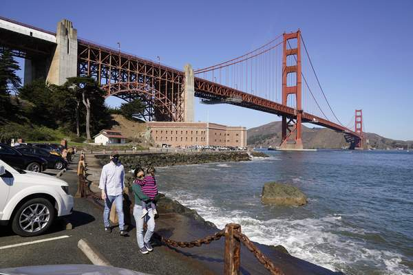 On a clear day people walk along a seawall with Fort Point and the Golden Gate Bridge in the background in San Francisco on Oct. 11, 2020. Wildfires that scorched huge swaths of the West Coast churned out massive plumes of choking smoke that blanketed millions of people with hazardous pollution that spiked emergency room visits and that experts say could continue generating health problems for years. An Associated Press analysis of air quality data shows 5.2 million people in five states were hit with hazardous levels of pollution for at least a day. (AP Photo/Eric Risberg)