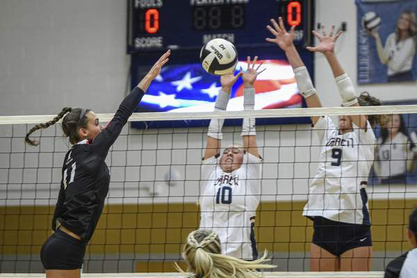 Bishop Luers junior Anna Parent attempts to spike as Garrett's Taylor Gerke, center, and Morgan Ostrowski defend.