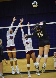 Mike Moore | The Journal Gazette  Concordia defenders Taylor Hepburn, left, and Mya Williams, center, guard the net asLeo junior Payton Rolfsen hits the ball in the first period during the IHSAA Volleyball Sectional at Bishop Dwenger on Tuesday.