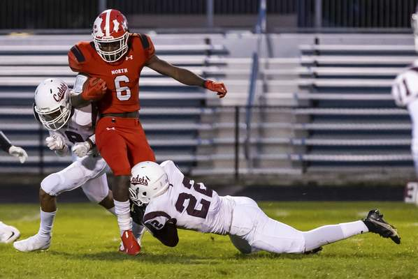 Josh Gales | Journal Gazette North Side senior Ja'Suan Lambert is tackled by Concordia senior Kam Johnson, left, and junior Dontrell Johnson, right, during the first quarter of the game at North Side High School on Friday.