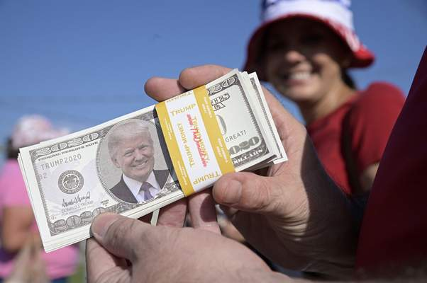 Associated Press Kevin Miltenberger hands out imitation money with the likeness of President Donald Trump before a campaign rally Friday in Ocala, Fla.