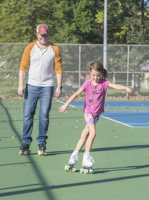 Michelle Davies | The Journal Gazette Brian Fletcher, rear, former World Team professional roller skater, watches as Ari Richwine, 8, works on her crossovers during a skating lesson Wednesday morning at Foster Park.