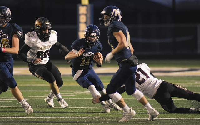Mike Moore | The Journal Gazette Norwell quarterback Eli Riley runs the ball in the first quarter against Columbia City at Norwell High School on Friday. Riley had four touchdowns in the Knights' comeback win.