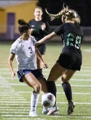 Rachel Bellwood | The Journal Gazette  Bishop Dwenger's Callie Burns fights for the ball againstBellmont at High School Girls Soccer Regionals hosted at Marion High School on Saturday