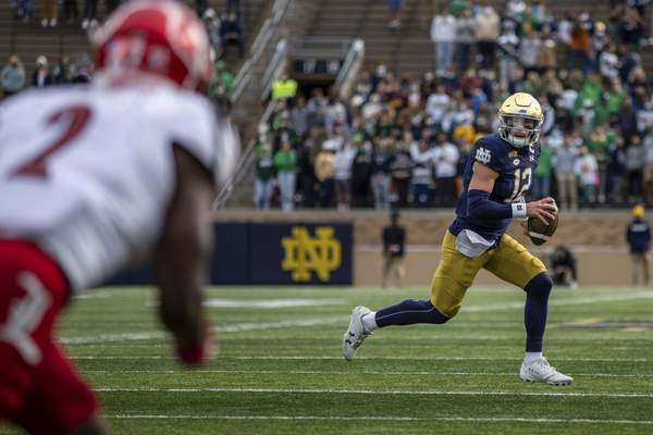 Notre Dame quarterback Ian Book scrambles with the ball Saturday against Louisville in South Bend.