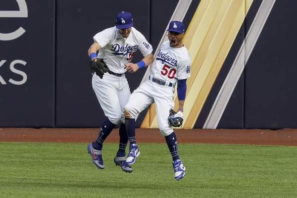 Associated Press Dodgers right fielder Mookie Betts celebrates with Cody Bellinger after robbing the Braves' Marcell Ozuna of a home run Saturday.