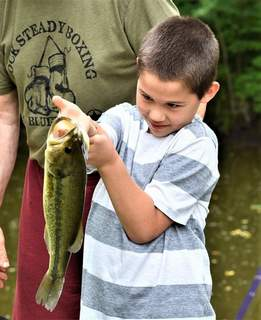 Courtesy photos Frank Daugherty, 8, of Terre Haute examines his largemouth bass prior to releasing it back into his grandfather Alan's pond near Bluffton.