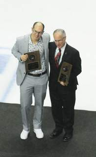 Emrick Justin A. Cohn | The Journal Gazette: Mike Emrick, right, and Lincoln Kaleigh Schrock are inducted into the Komets Hall of Fame at a game at Memorial Coliseum in March.