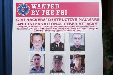 Russian Hackers Charged A poster showing six wanted Russian military intelligence officers is displayed before a news conference at the Department of Justice, Monday, Oct. 19, 2020, in Washington. (AP Photo/Andrew Harnik, pool) (Andrew Harnik