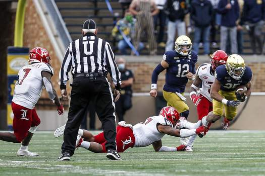 Ian Book, Kyren Williams Atlantic Coast Conference Chris Tyree, right, breaks a tackle for Notre Dame against Louisville on Saturday, as Ian Book  follows. (Notre Dame Athletics)