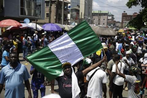 Nigeria Police Protest People hold banners as they demonstrate on the street to protest against police brutality, in Lagos, Nigeria, Tuesday Oct. 20, 2020. (AP Photo/Sunday Alamba) (Sunday Alamba STF)