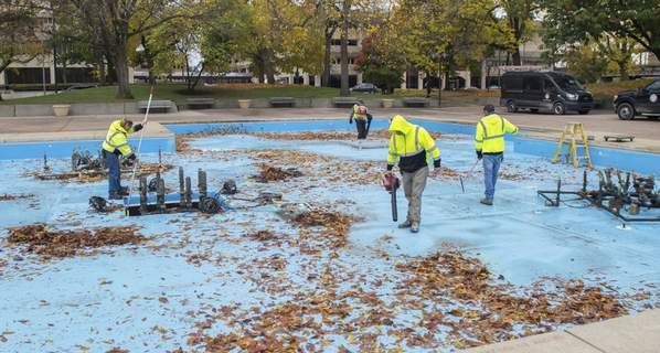 Michelle Davies | The Journal Gazette Fort Wayne Parks crew members work on cleaning up Freimann Square's fountain to prepare it for winterization Tuesday morning.