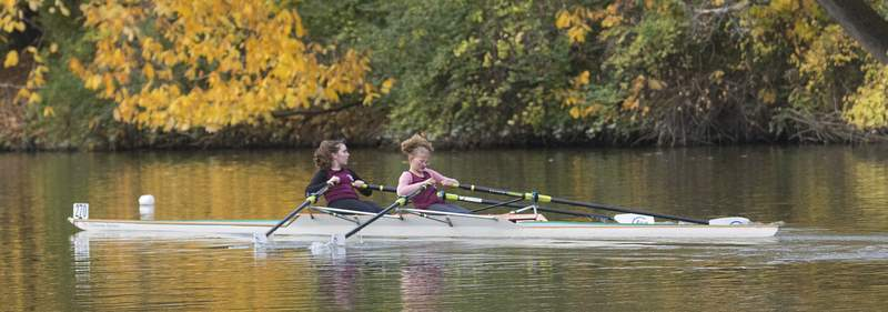 Michelle Davies   The Journal Gazette  Vivian Crews, left, a freshman at Bishop Dwenger, and Elliot McBride, right, a sophomore at Concordia High School, compete in Saturday's first annual fall regatta, Row the Mauma Jo. The event, hosted by Glorious Gate Rowing Association, went from the starting point at Shoaff Park to the finish line at the Venderley Family Bridge across from Purdue Fort Wayne.