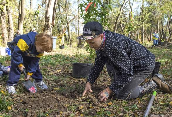 Michelle Davies   The Journal Gazette  Malakai Backus, 5, left, and Dakota Hoehn, both of Fort Wayne, work together to plant trees Saturday morning at Save Maumee's 3-Day Tree Planting event, commemorating their 15th year of saving the rivers.