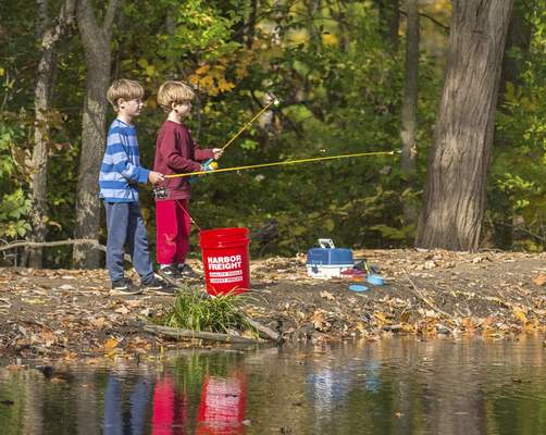 Michelle Davies   The Journal Gazette Caleb Lineberry, 9, and brother C.J., 7, fish together Friday morning for rainbow trout at the pond in Shoaff Park.