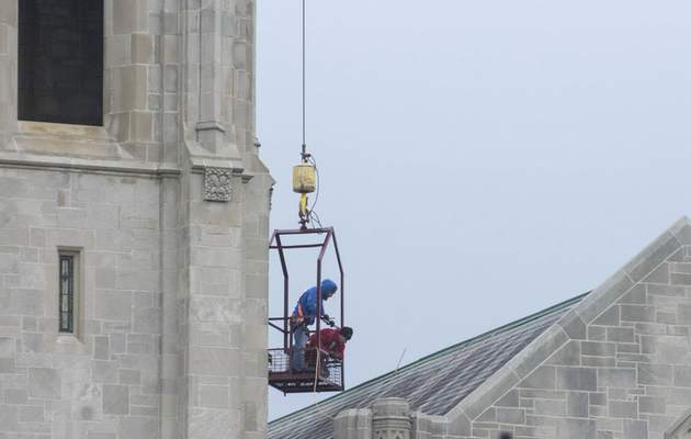 Michelle Davies   The Journal Gazette  Bobby Wiseman, foreman, and Chris Bloomfield, laborer, both with Tri-State Lightning Protection, install lightning rods on Plymouth Congregational Church Tuesday morning.