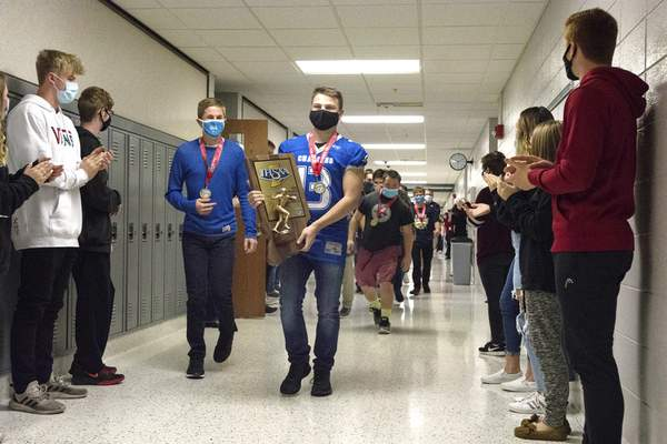 Michelle Davies   The Journal Gazette  Carroll High School senior Logan Smith leads his flag football team through the school halls Wednesday morning to celebrate the team's State Champion runner-up status. Smith, along with teammate Casey Bane, won the mental attitude award.