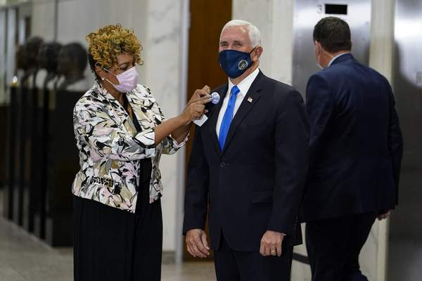Vice President Mike Pence gets an I Voted sticker after casting his ballot during early voting in Indianapolis, Friday, Oct. 23, 2020. (AP Photo/Michael Conroy)