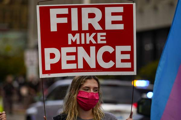 A protester carries a Fire Mike Pence sign as she and others march around the City-County Building after Vice President Mike Pence and his wife Karen cast their ballots during early voting in Indianapolis, Friday, Oct. 23, 2020. (AP Photo/Michael Conroy)