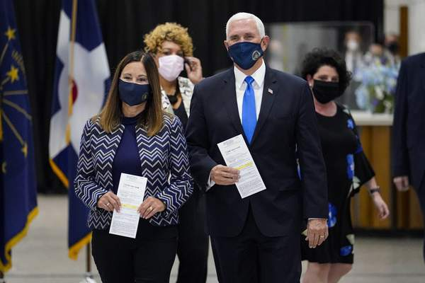 Vice President Mike Pence and his wife Karen walk to cast their ballots during early voting in Indianapolis, Friday, Oct. 23, 2020. (AP Photo/Michael Conroy)