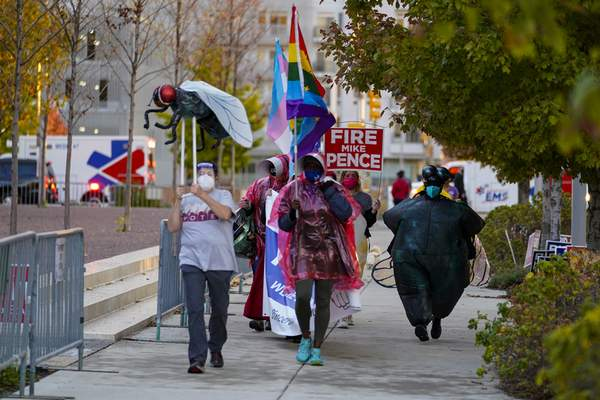 Protesters march around the City-County Building after Vice President Mike Pence and his wife Karen cast their ballots during early voting in Indianapolis, Friday, Oct. 23, 2020. (AP Photo/Michael Conroy)
