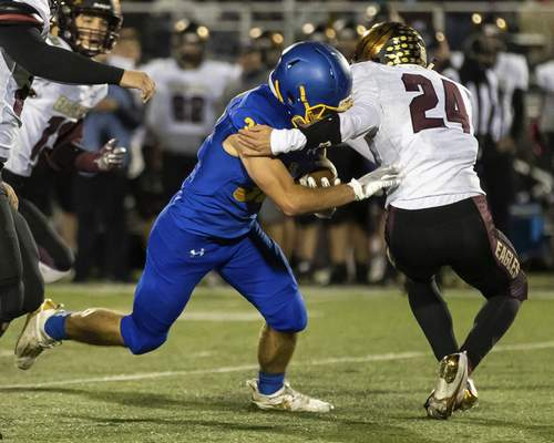Josh Gales   Journal Gazette Columbia City sophomore Ethan Sievers tackles East Noble senior Justin Marcellus during the first quarter of the sectional game at East Noble High School on Friday.