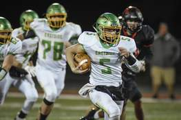 Mike Moore | The Journal Gazette Eastside quarterback Laban Davis carries the ball in the second quarter Friday night against Bluffton.