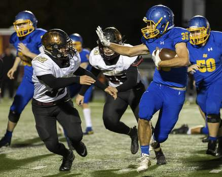 Josh Gales   Journal Gazette East Noble senior Justin Marcellus carries the ball against Columbia City sophomore Josh Arntz during the second quarter of the sectional game at East Noble High School on Friday.