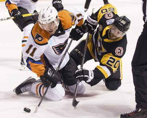 FILE - In this March 16, 2019, file photo, Lehigh Valley Phantoms' Steven Swavely (11) moves the puck past the Wilkes-Barre/Scranton Penguins' Jarrett Burton after a faceoff during an AHL hockey game at Mohegan Sun Arena in Wilkes-Barre, Pa. The American Hockey League has canceled the rest of its season because of the coronavirus pandemic. President and CEO David Andrews announced the league 'has determined that the resumption and completion of the 2019-20 season is not feasible in light of current conditions.' The AHL's Board of Governors made that determination in a conference call Friday, May 8, 2020. (Christopher Dolan/The Citizens' Voice via AP, File)