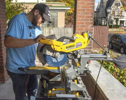 Michelle Davies | The Journal Gazette Spencer Sistevaris with Sistevaris Builders cuts trim pieces Wednesday for a home renovation on Rockhill Street.