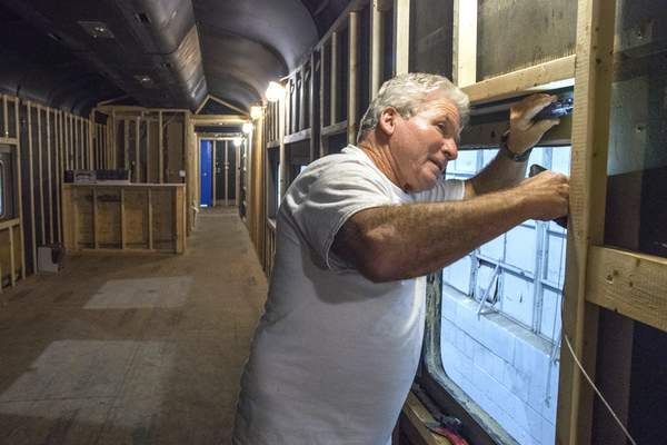 Michelle Davies | The Journal Gazette Steve Hinen works on reinstalling windows in a former hospital train car, being converted into a club car.