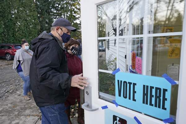 A couple enter a polling station to vote on Election Day at the Middlefield Community Senior Center in Middlefield, Ohio, Tuesday, Nov. 3, 2020. (AP Photo/Tony Dejak)