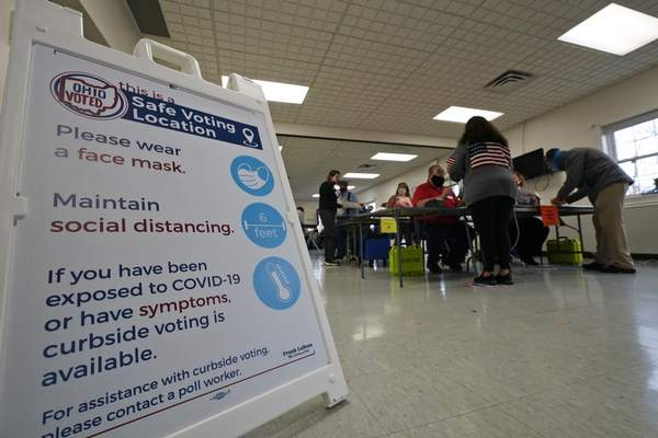 A social distancing sign rests on the floor at the Middlefield Community Senior Center as voters pick up their ballots on Election Day in Middlefield, Ohio, Tuesday, Nov. 3, 2020. (AP Photo/Tony Dejak)