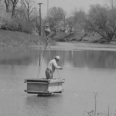 April 28, 1967: Bonn B. Hill is seen fishing from the bucket of a crane at the confluence of the city's rivers. (Journal Gazette File photo)