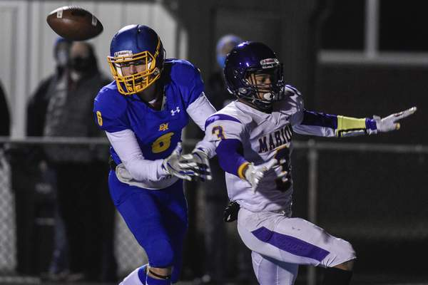 Photos by Mike Moore | The Journal Gazette A pass intended for East Noble wide receiver Rowan Zolman, left, is broken up by Marion defensive back Josh Balfour during Friday night's regional championship game.
