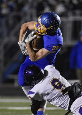East Noble running back Justin Marcellus is tackled in the first quarter by Marion's David Jones in Kendallville on Friday night.