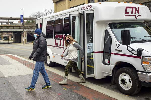 Mike Moore | The Journal Gazette Guests attending the Hop On Brew Tour downtown on Saturday step off a CTN provided transport bus headed for the Landing Beer Company.